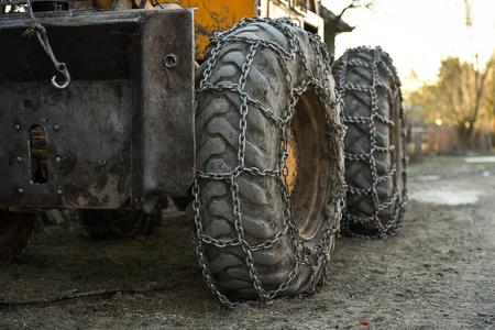 Photo detail with snow tire chains on big truck wheel Standard-Bild - 124314094