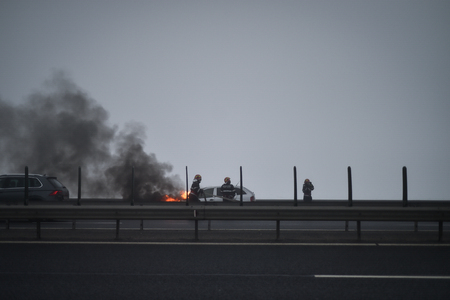 Firemen try to extinguish a burning car on a highway