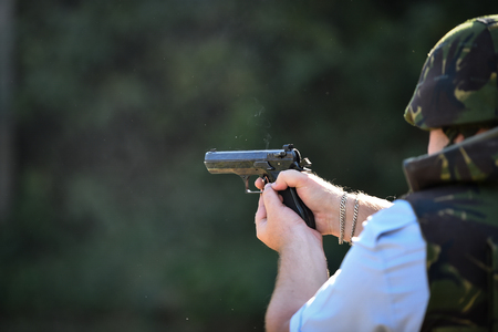 Outdoor target shooting with a 9mm pistol in a shooting range