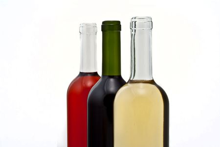 upper half: Three bottles of red, rose, and white wine in a row at an angle, upper half of bottles. Stock Photo