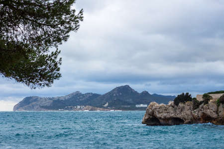 The coast of Mallorca in Cala Ratjada. Mediterranean sea, rocks and mountain. Imagens