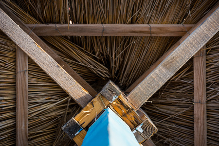 Wooden sunshade, straw umbrella with a blue foot, view from below Zdjęcie Seryjne