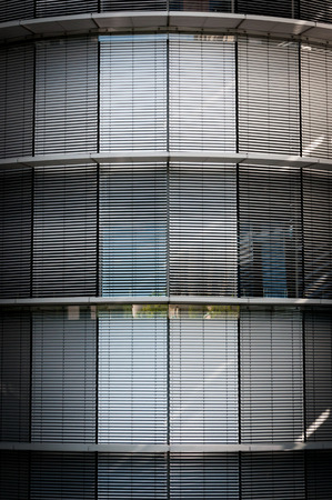 Windows with white shutters and reflections in the modern building in Berlin, Germany