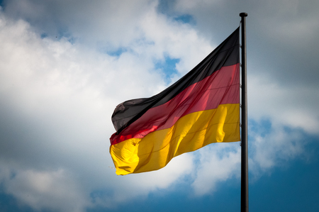 German flag fluttering in the wind with the blue sky with white clouds in a background
