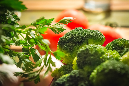 Parsley and broccoli with tomatoes in the background