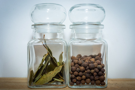 Bay leaves and allspice in a glass jar on the wooden shelf Zdjęcie Seryjne