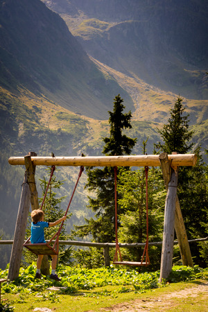 A little boy is swinging on a swing in the mountains