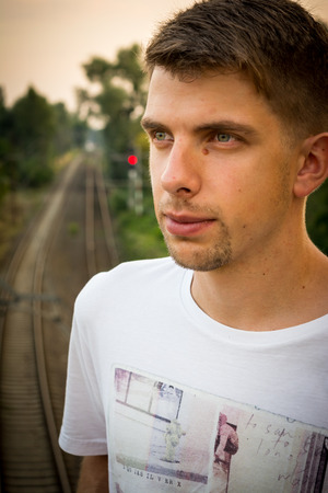 Young man is standing and looking away with railway in the background