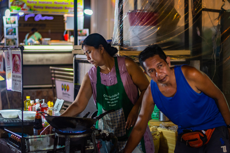 BANGKOK, THAILAND - NOVEMBER 2018: Thai muslim couple are preparing food and cooking in the evening on the night market Publikacyjne