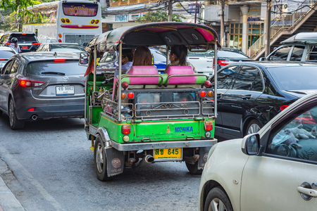 BANGKOK, THAILAND - NOVEMBER 2018: Auto rickshaw (tuk-tuk) with passengers on the sunny day in Bangkok, Thailand