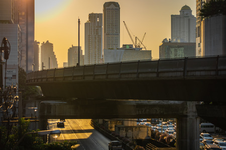 BANGKOK, THAILAND - NOVEMBER 2018: Orange sunset over the street of Bangkok and the skytrain railroad, Thailand