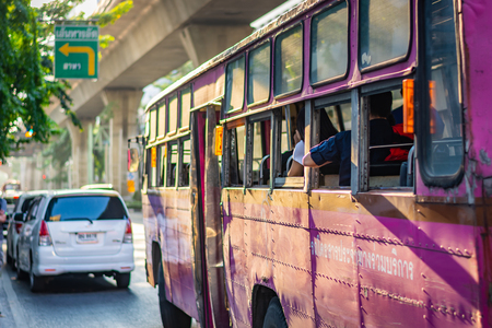 BANGKOK, THAILAND: Pink bus with passengers is walking along the street in Bangkok, Thailand Zdjęcie Seryjne