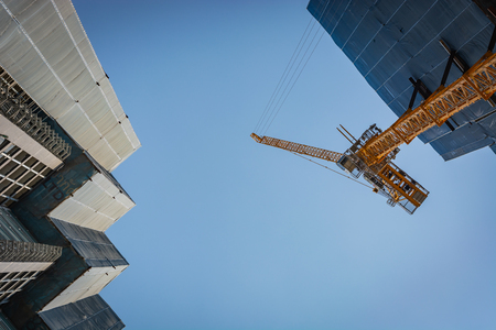 Cranes and scaffolding at a construction site in Bangkok, Thailand
