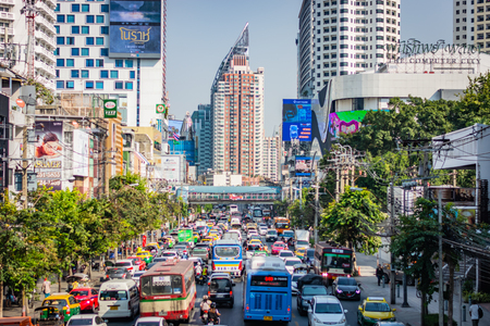 BANGKOK, THAILAND - NOVEMBER 2018: Street in Bangkok (Thailand), a big traffic jam, a lot of cars and buses, a sunny day, buildings, trees