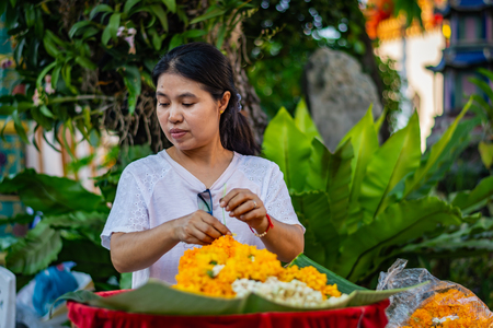 BANGKOK, THAILAND - NOVEMBER 2018: Woman florist arranges orange flowers at the Buddhist temple of Wat Pho in Bangkok, Thailand