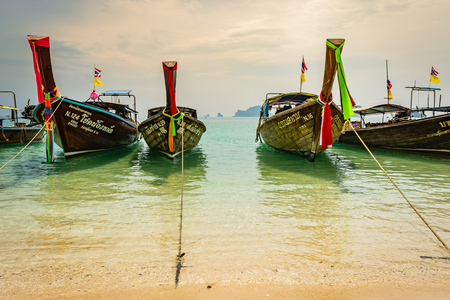 KRABI, THAILAND - NOVEMBER 2018: Thai traditional wooden boats with ribbon decoration at ocean shore near Krabi, Thailand