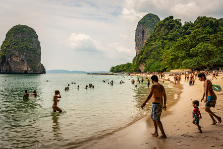 KRABI, THAILAND - NOVEMBER 2018: Beach Hat Phra Nang near Krabi, Thailand, sunny beach, crowd of people, bathing tourists, green trees and clouds in the background