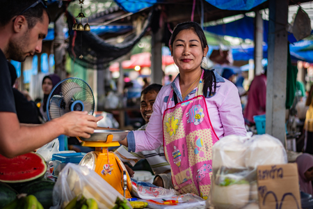 KOH LANTA, THAILAND - NOVEMBER 2018: Young woman sells fruit on the island of Koh Lanta, a woman accepts a payment from a man, between them stands a weight, Thailand Publikacyjne