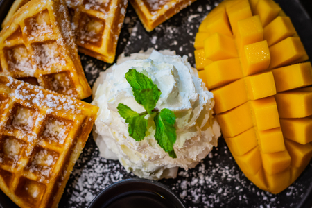 Whipped cream, mint leaf, mango and waffles sprinkled with powdered sugar served on a black plate
