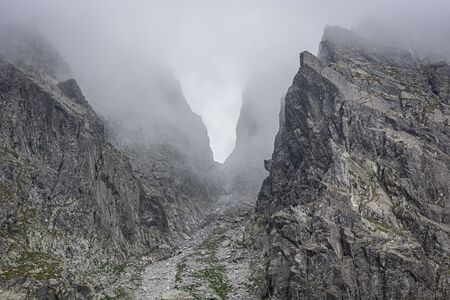 Mountain pass surrounded by fog, gray rocks in the mountains, passage between the peaks, invisible due to low clouds, in Tatra Mountains