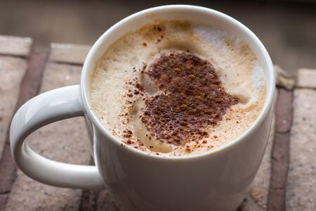 Cup of art cappuccino coffee. A cup of coffee with heart pattern in a white Stock Photo
