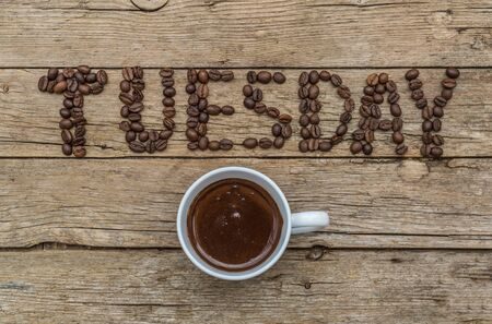 Cup of coffee on wooden background and TUESDAY coffee beans
