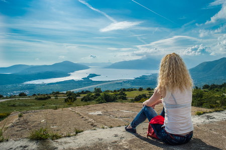 Curly blonde girl sitting and looking out to sea in Montenegro