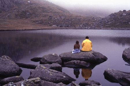 snowdonia: Adult man and young girl sitting on the shore of mountain lake Llyn Bochlwyd in Glyderau, Snowdonia