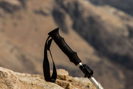 Trekking pole for hiking with the mountains in the background. Plastic and aluminum handle