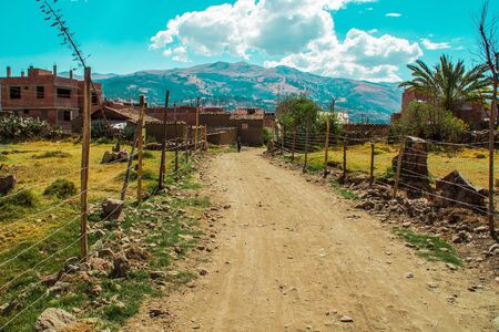 Typical unpaved street of a Latin American country in the background mountains and blue sky with clouds.