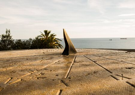 Sundial on a rock table with the sea in the background Stock Photo