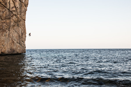 Climbing into the sea without a rope. Climbing mode called Psicobloc Stock Photo