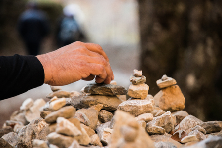 Stones piled up on the mountain with one hand putting them in place. Symbol of peace Stock Photo
