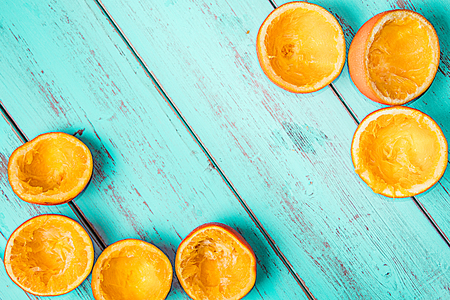 Oranges squeezed on a rustic blue background