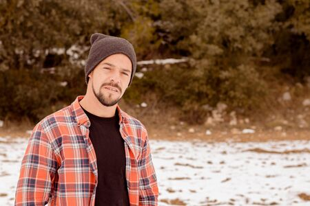 Pensive man with beard plaid t-shirt, hat and casual clothing. A young and carefree lifestyle. Snow bottom Stock Photo