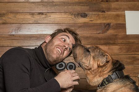 Young man playing with his dog at home.Dog of shar-pei breed brown color