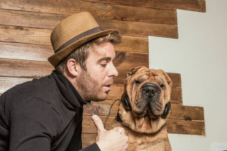 Dog with music headphones, and a guy playing with it. Funny picture with a Sharpei dog