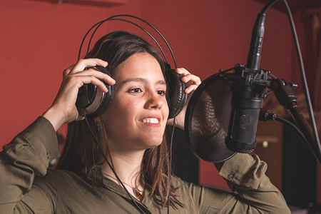 Girl singing with a microphone and headphones. With a cheerful and smiling expression