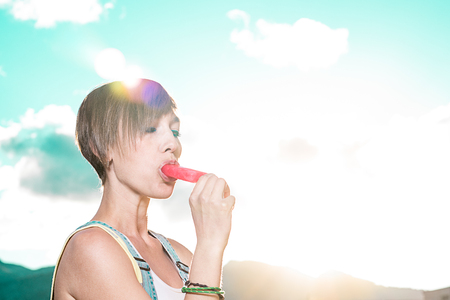 Young girl eating an ice-cream popsicle with the sun in the background