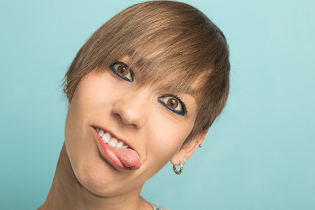 Woman with short hair sticking out her tongue with funny expression