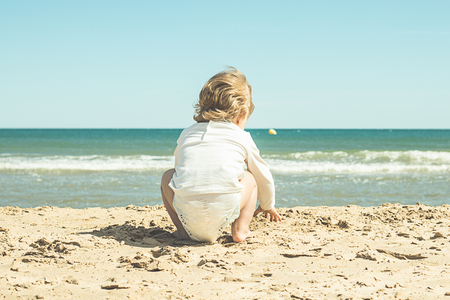 Little girl in diapers on the beach. Lovely girl on the beach Banque d'images