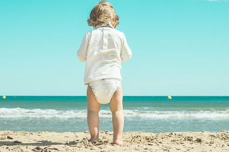 Little girl in diapers on the beach. Lovely girl on the beach Stock Photo