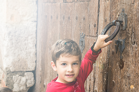 Child knocking on an old door in the street