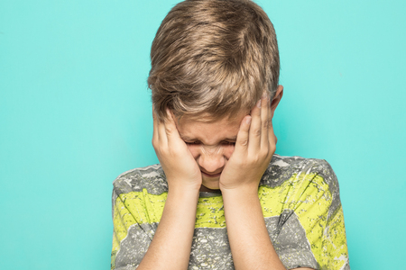 A child expressing a firing squad with his hands on his face