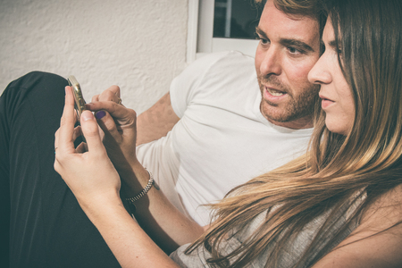 Guy and a girl watching her cell phone sitting on a couch. Young couple looking at the mobile phone Stock Photo