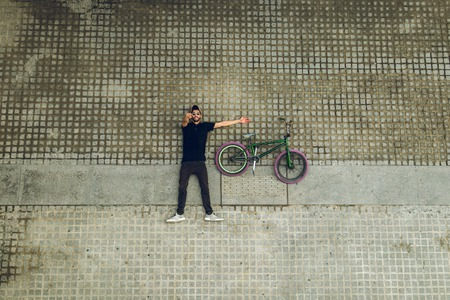 Guy looking at the camera with a bmx bike on the street. Guy with a bmx for the city Reklamní fotografie - 109942785