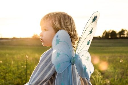 Little girl in a butterfly costume. Concept of children playing and happy Stock Photo
