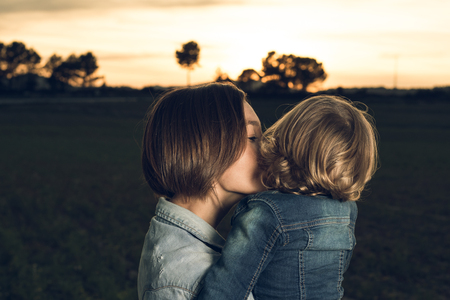 Close-up of a mother hugging her little daughter at sunset. Love between mother and young daughter Imagens