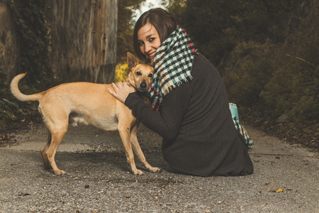 Happy woman stroking her dog. Concept of friendship between dog and person