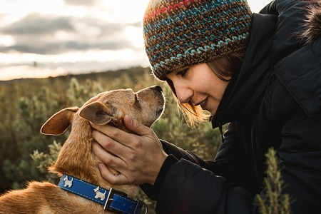 Young woman happy, kissing and hugging her dog. Concept of friendship between woman and dog